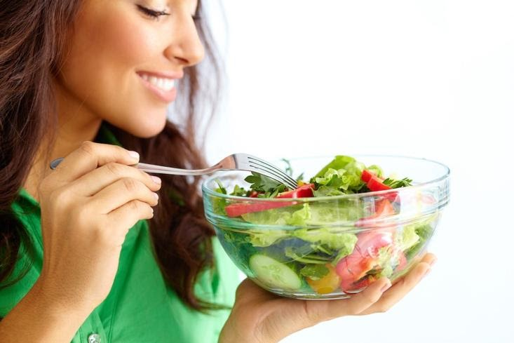 A person eating a salad  Description automatically generated with medium confidence